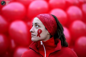 Student Aline Hubin stands in front of red balloons with a red ribbon painted on her face during a demonstration at Edinburgh University on World Aids Day in Edinburgh, Scotland December 1, 2006. REUTERS/David Moir